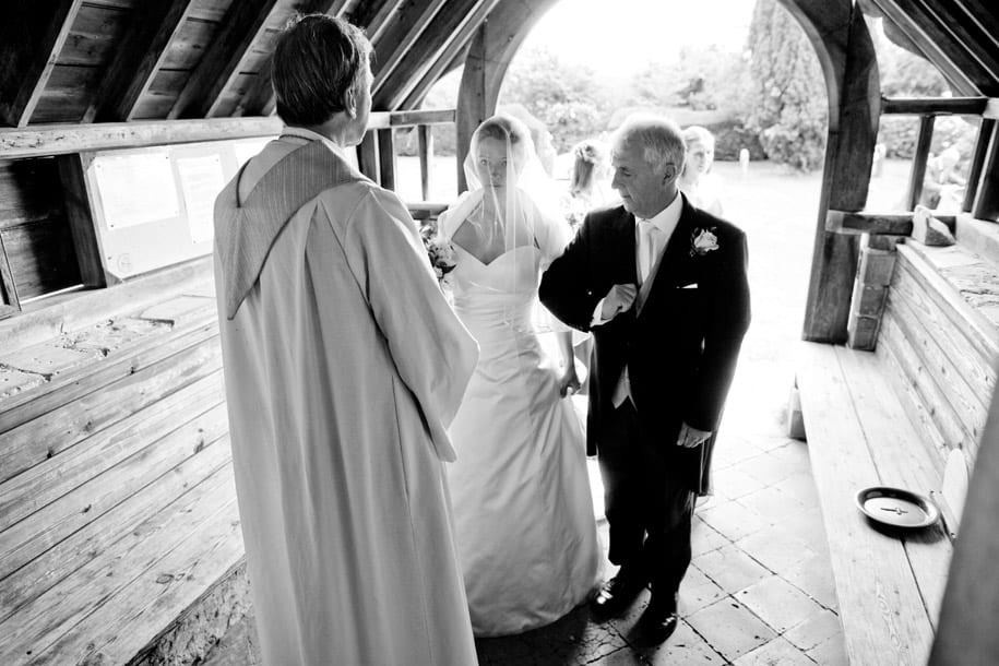 Bride takes her father's arm as she perpares to enter Dogmersfield church