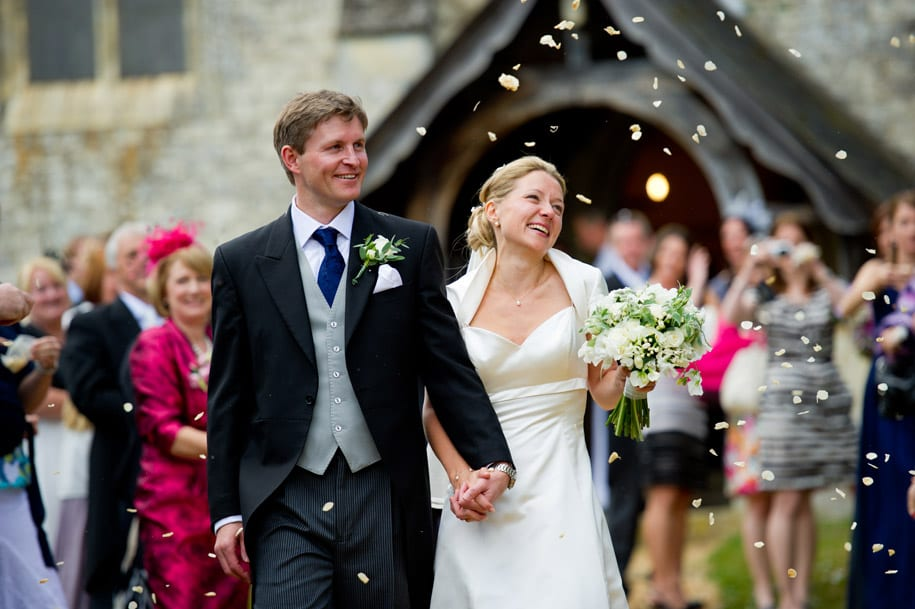 Bride and groom walk through confetti at Dogmersfield church