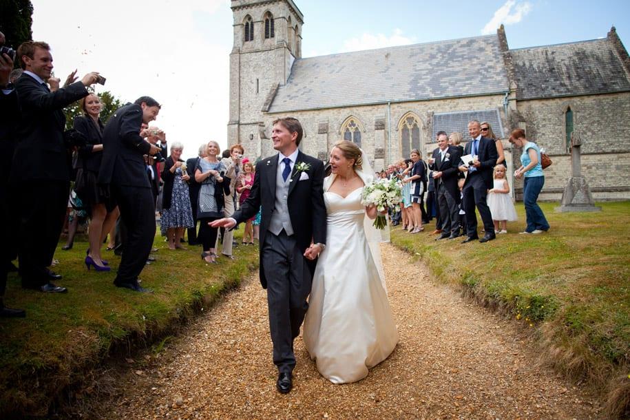 Bride and groom walk through confetti at Dogmersfield church in Hampshire