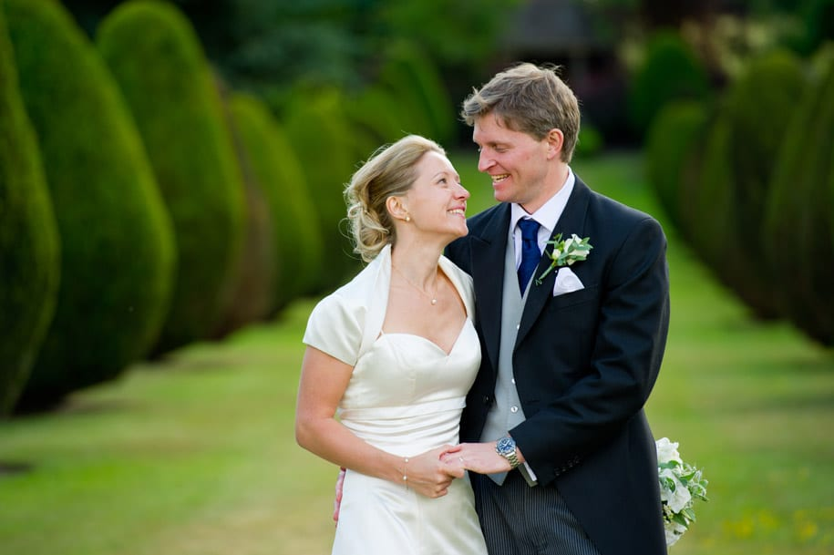 Bride and groom share a joke in the grounds of Elvetham hotel
