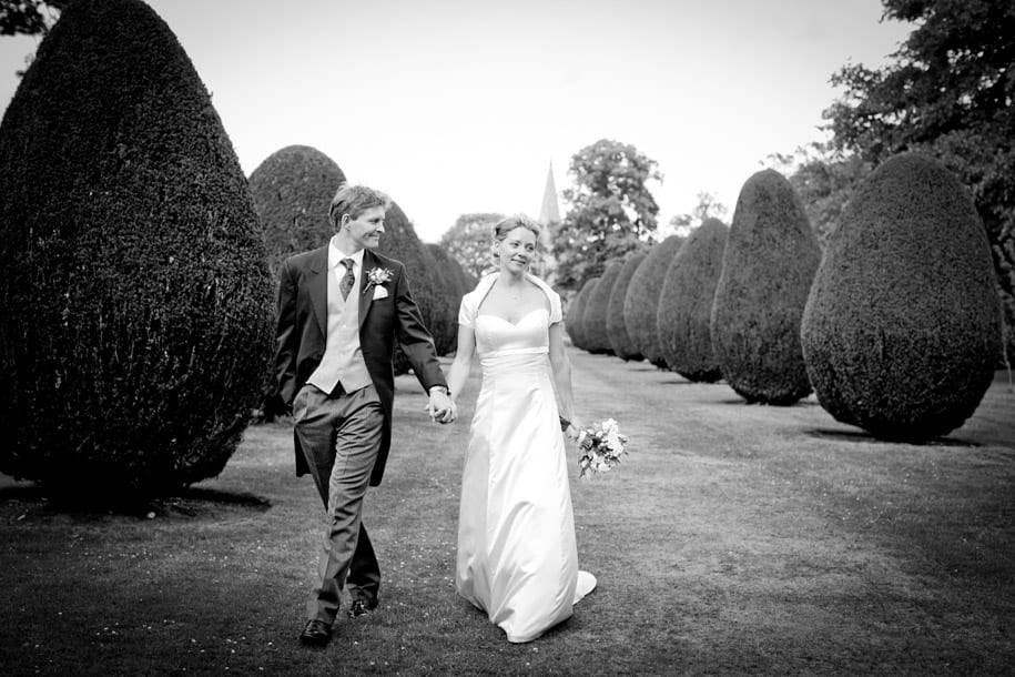 Bride and groom walk the grounds at Elvetham hotel
