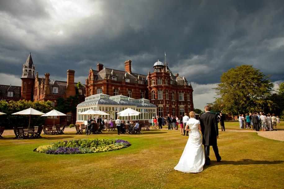 Bride and groom walk near Elvetham hotel under stormy skies