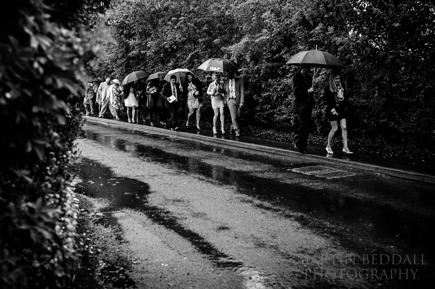 Wedding guests head to the wedding reception in the rain