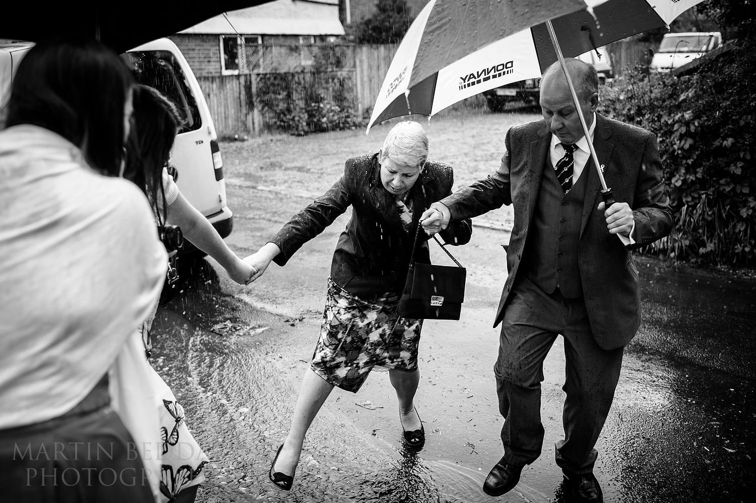 Helping a wedding guest cross a puddle