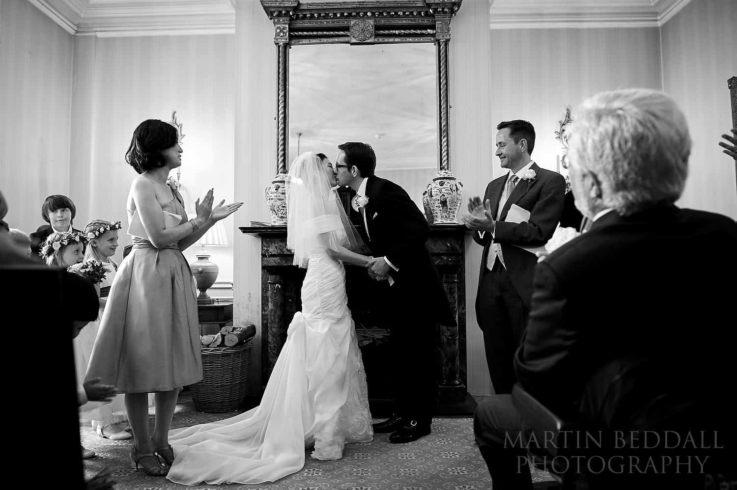 Bride and groom kiss after the ceremony at Ockenden manor