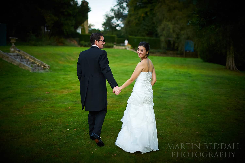 Bride and groom walk in the grounds at Ockenden Manor