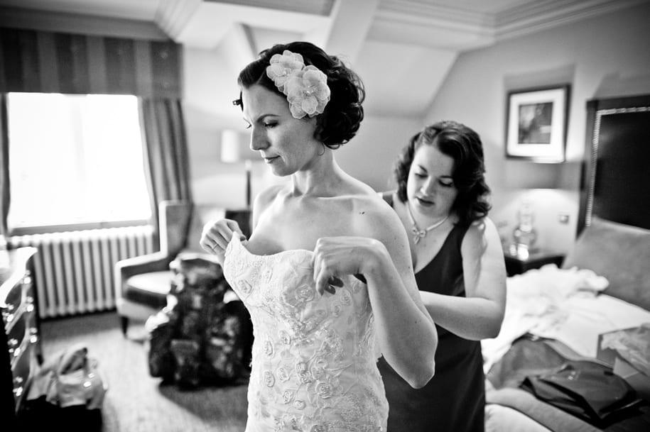 Bridesmaid helps bride into her wedding dress