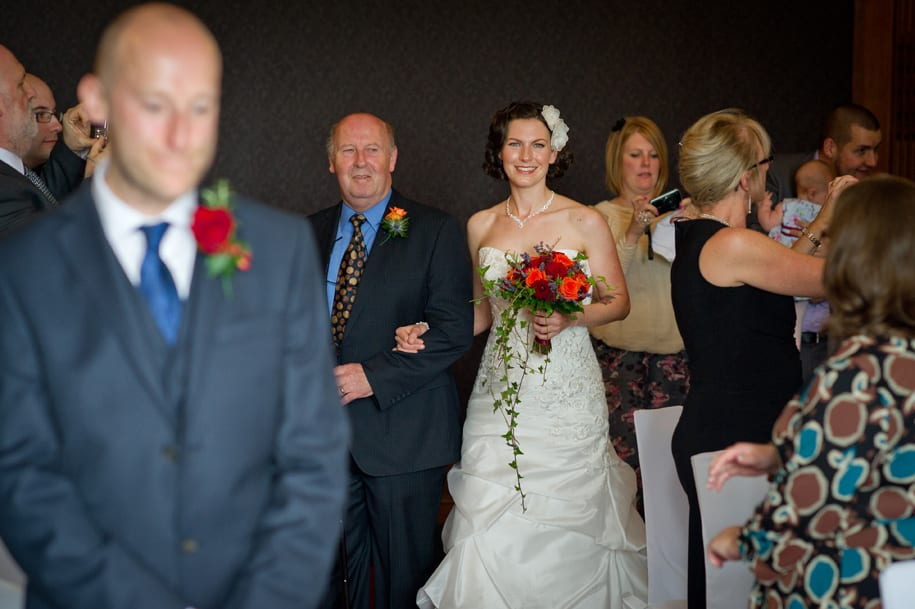 Bride walks down aisle with her father and groom looks nervous