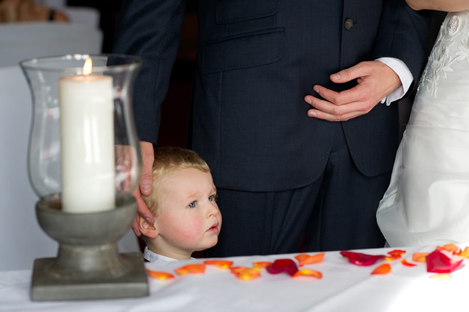 Bride and groom's son joins the ceremony, peering over the table