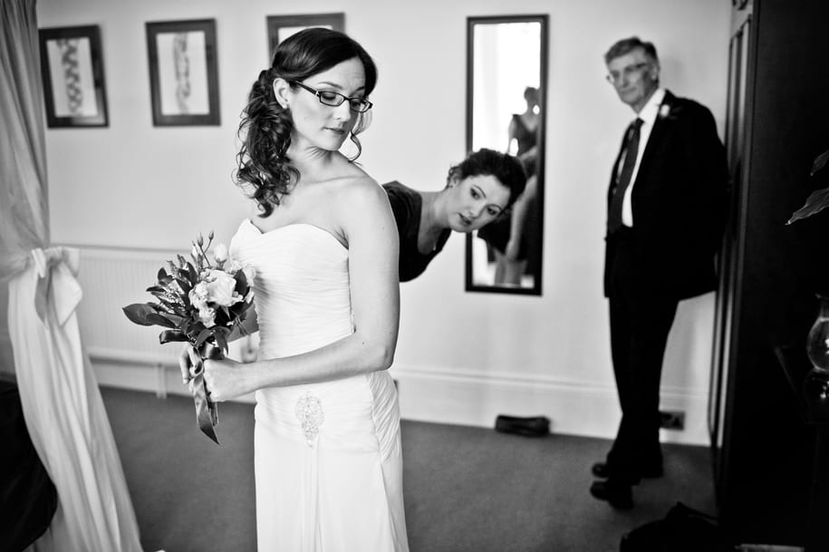 Father looks on as bride gets ready at Claremont hotel in Hove