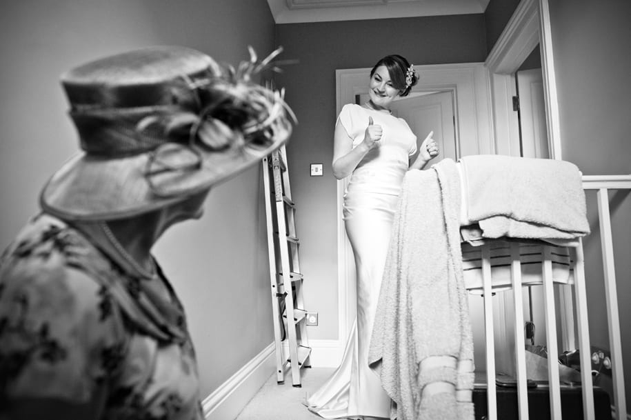 Bride gives the thumbs up to her mother as she gets ready