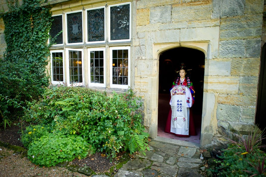 Bride waits at Ockeneden Manor before a Korean wedding ceremony