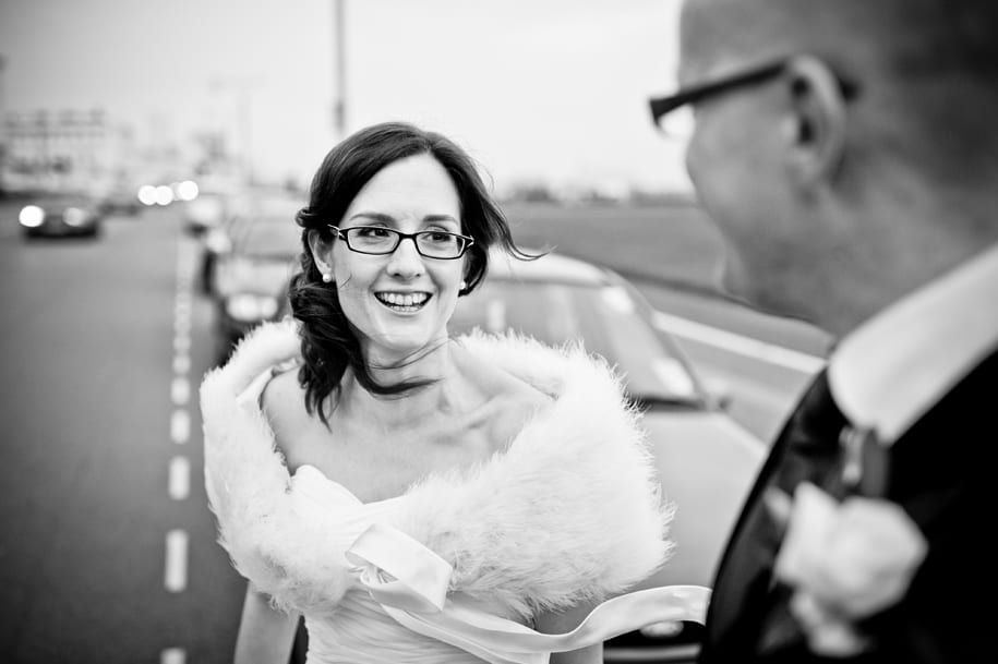 Bride shares a joke on the Hove seafront with her husband