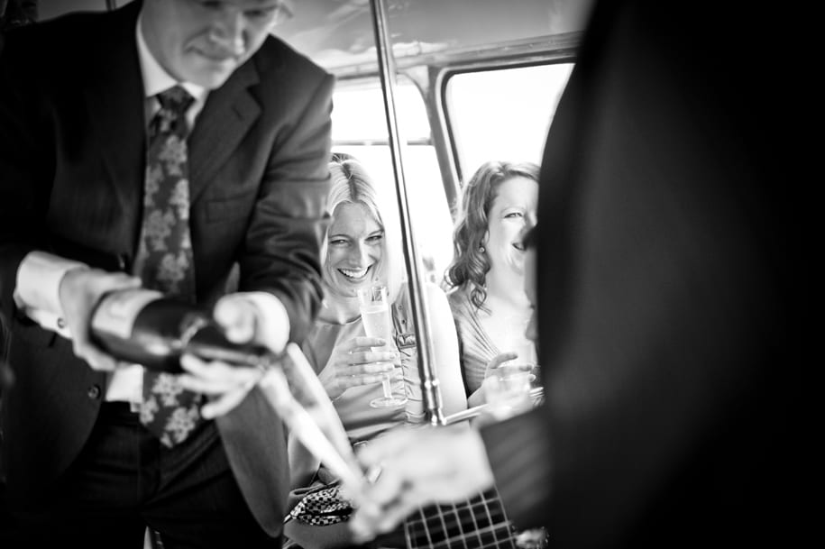 Champagne is poured for wedding guests on a Routemaster bus