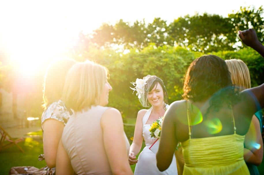 Bride shares a joke with her friends in the evening sunlight