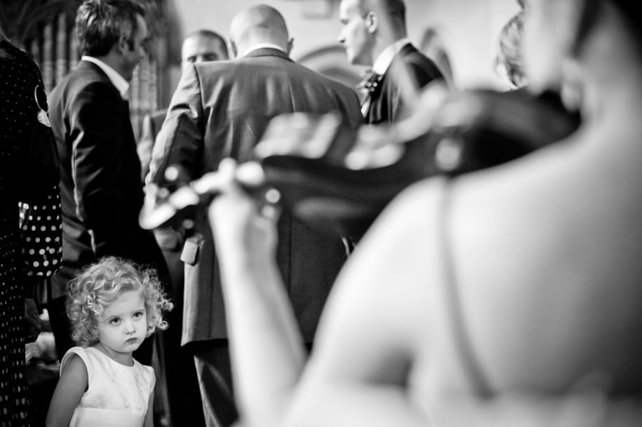 Young wedding guest watches the musicians during the reception at Nutfield Priory