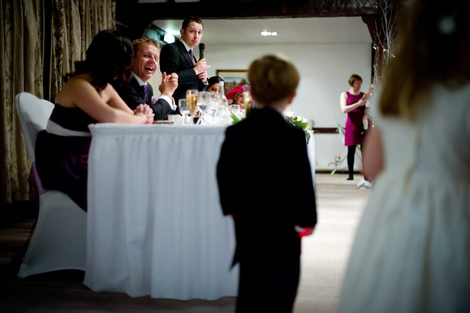Bridal party looks towards the page boy during speeches at Burford Bridge hotel