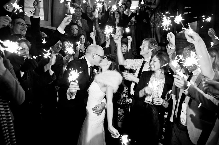 Bride and groom kiss surrounded by wedding guests with sparklers