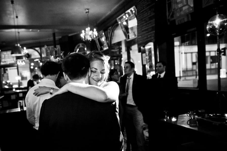 Bride and groom embrace at their wedding reception in a pub in London