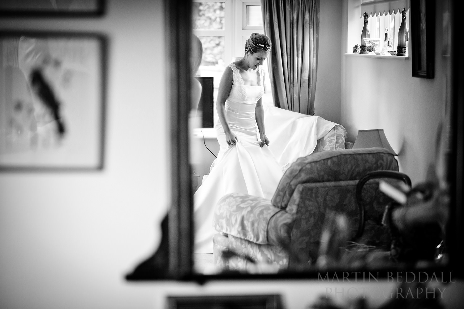 Bride in her wedding dress reflected in the mirror