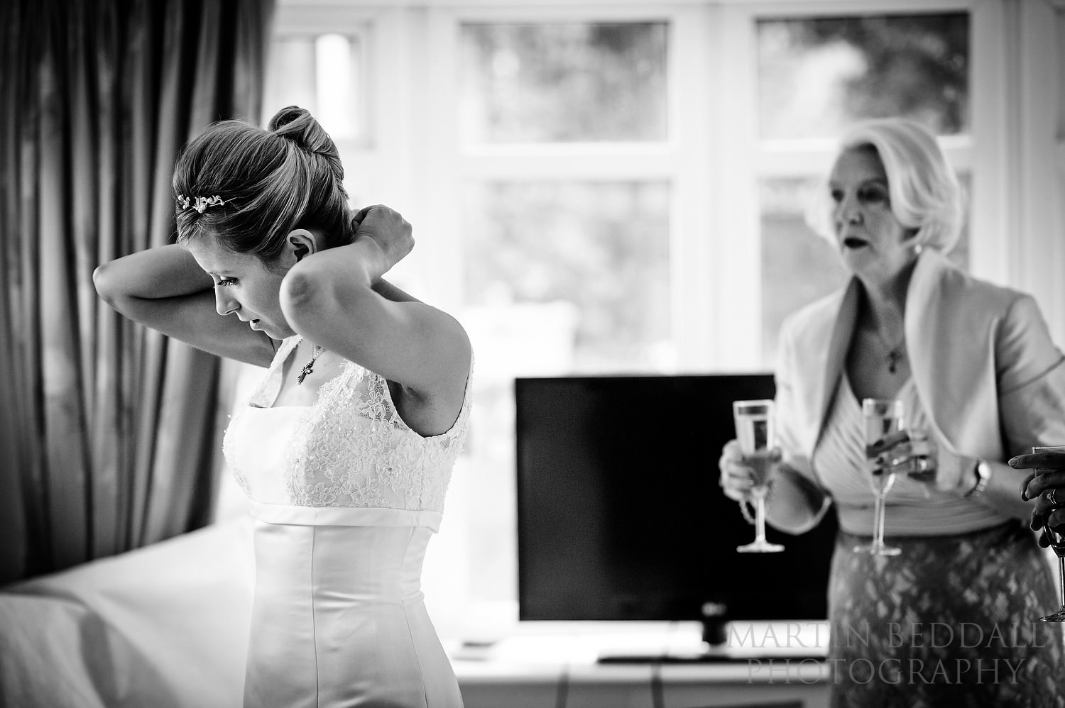 Bride doing up her necklace