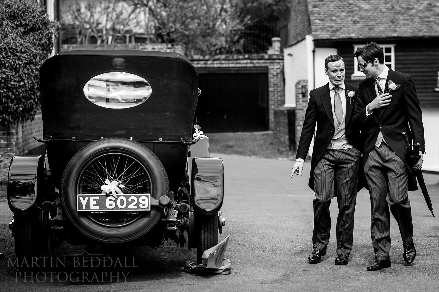Groom spots that the vintage wedding car has destroyed a traffic cone