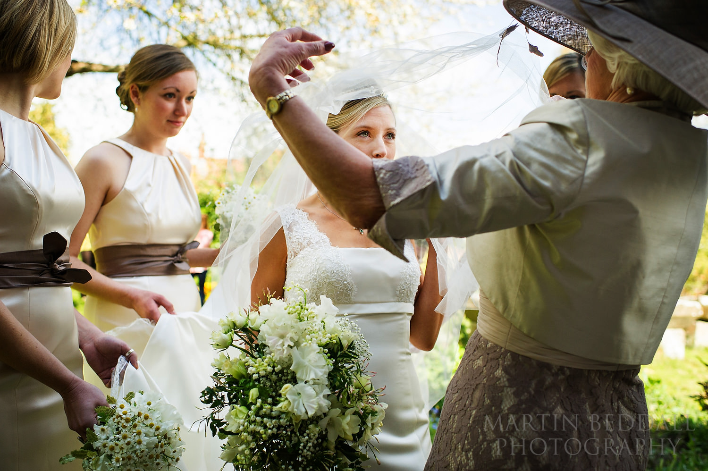 Bride's mother adjusts the bride's veil
