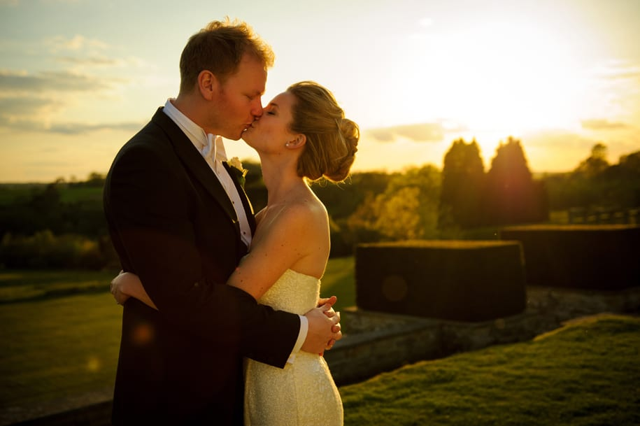 Brdie and groom kiss in gorgeous evening sunlight at Buckhurst park wedding