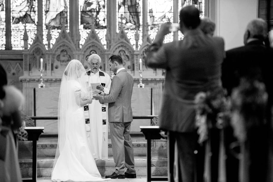 Groom places ring on bride's finger at St Mary's in Horsham