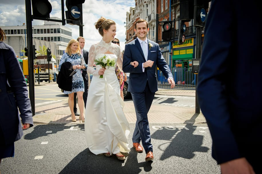 Elegant bride and groom stroll with guests in Putney