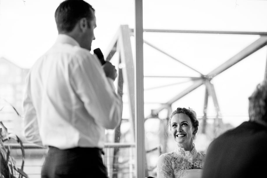 Bride smiles at the groom talks about her in his speech