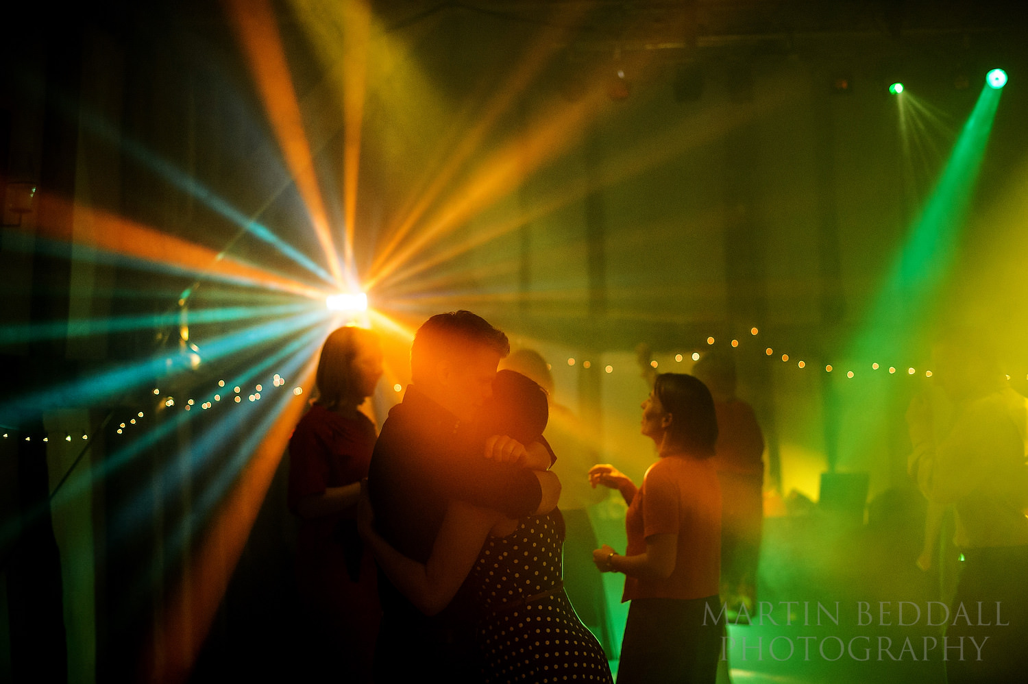 Guests hug on the dance floor at Old Greens Barn