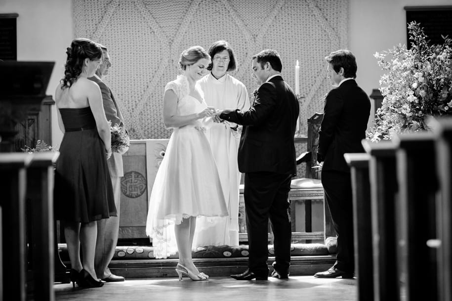 Bride places ring on groom's finger at Girton College chapel