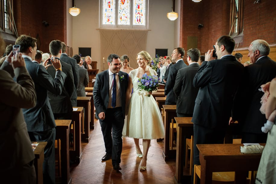 Bride and groom walk back down the aisle at Girton College wedding