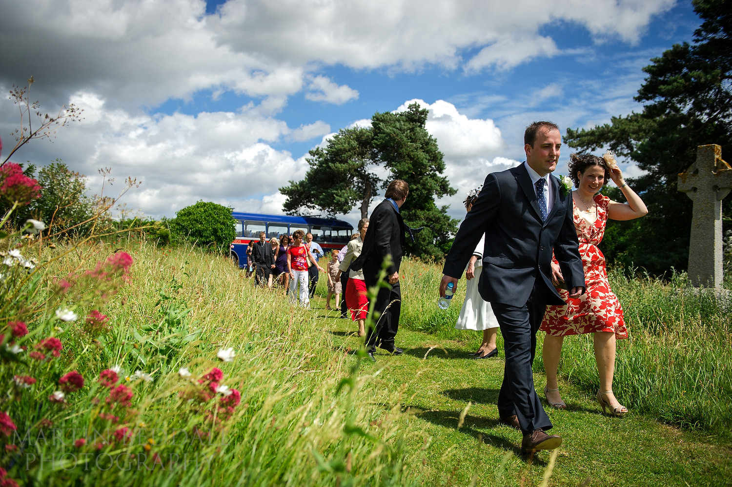 Groom leads the wedding guests to the Suffolk church