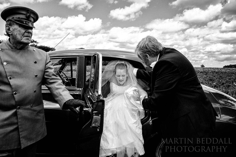Bride bumps her head on the wedding car