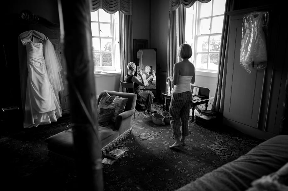 Bride watches her mother adjsuting her hair in the mirror