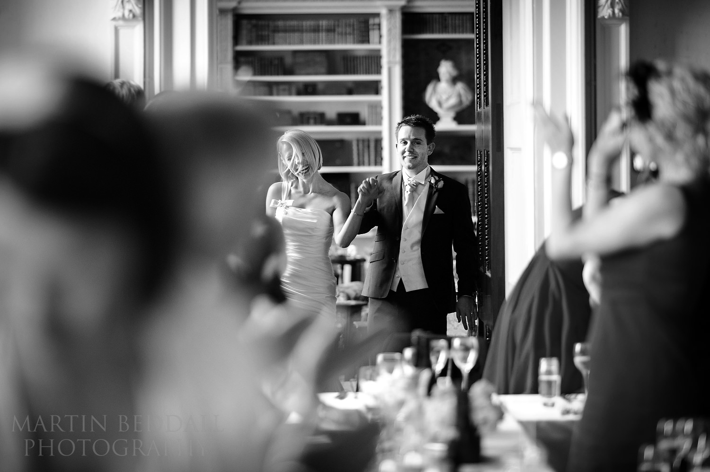 Bride and groom make an entrance to dinner at Kirtlington Park