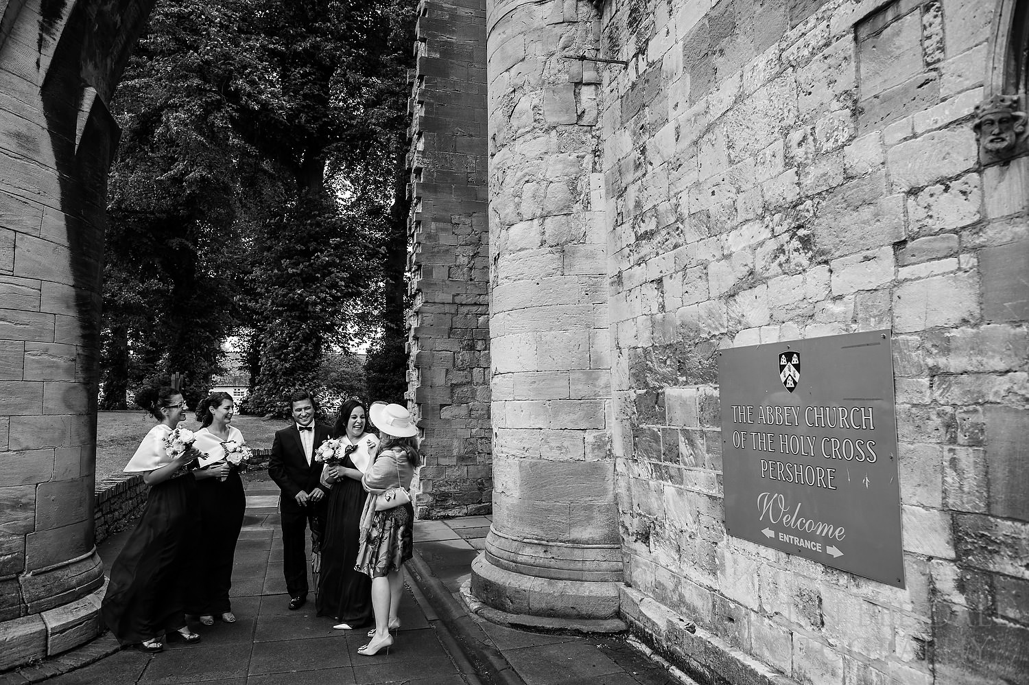 Bridesmaids wait outside the Abbey Church of the Holy Cross Pershore