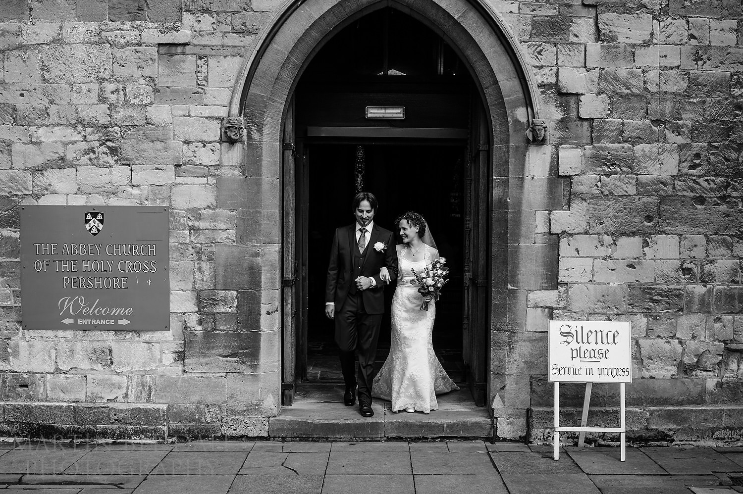 Bride and groom walk out of Pershore Abbey