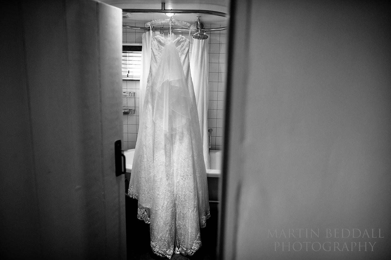 Bride's wedding dress hanging in the bathroom at Ridge Farm