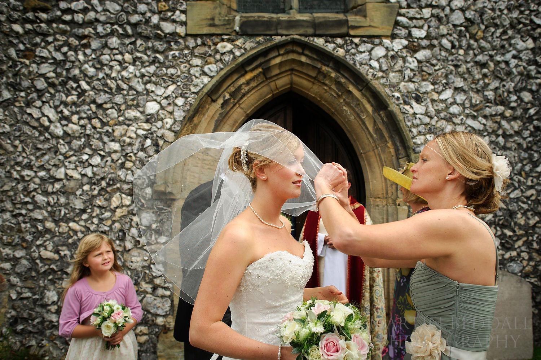 Sister adjusts bride's wedding veil