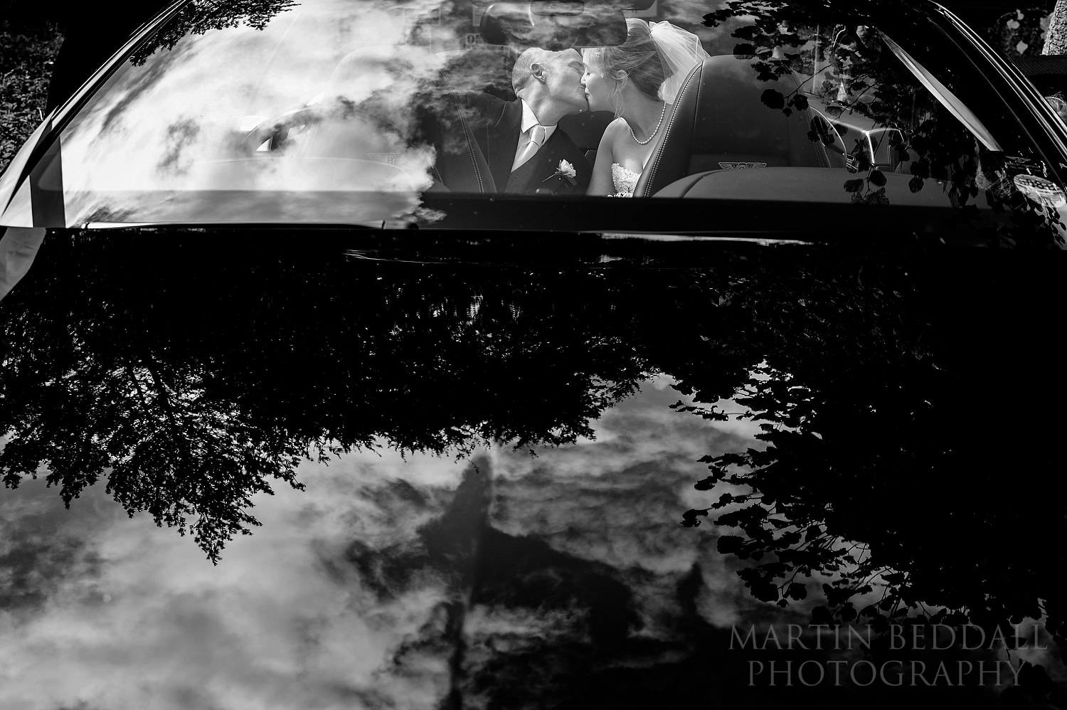 Bride and groom kiss in the wedding car
