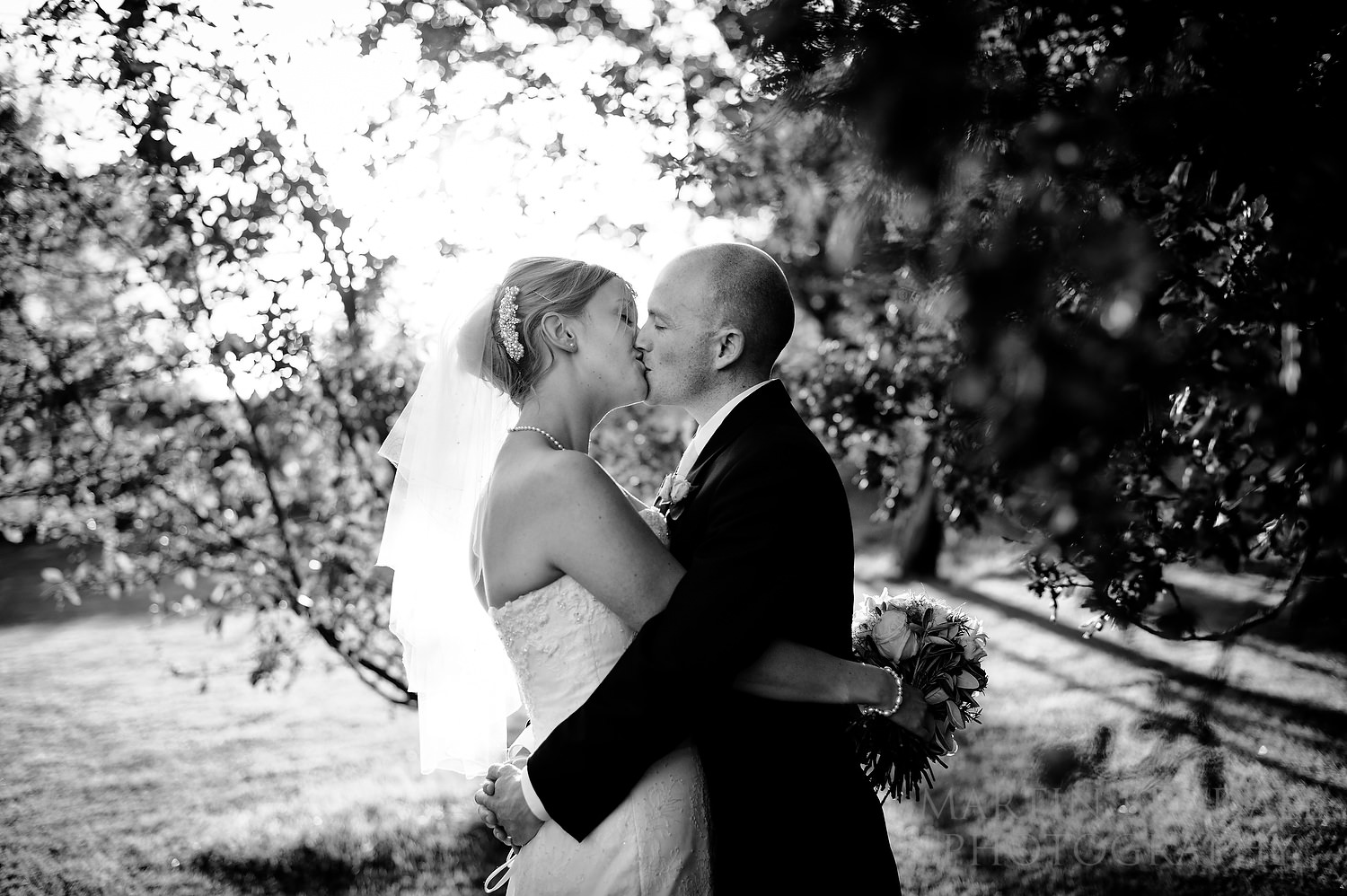 Bride and groom kiss in the grounds of Ridge Farm