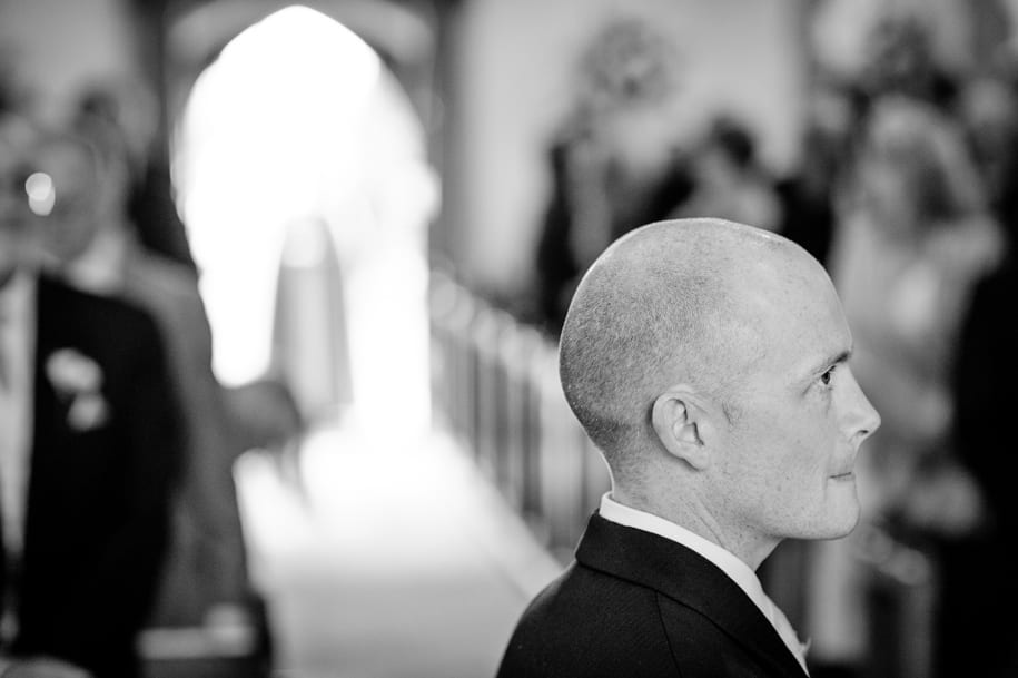 Groom bites his lip as he waits for the bride's entrance