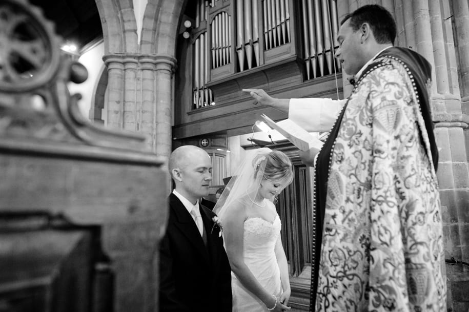 Kneeling bride and groom are blessed