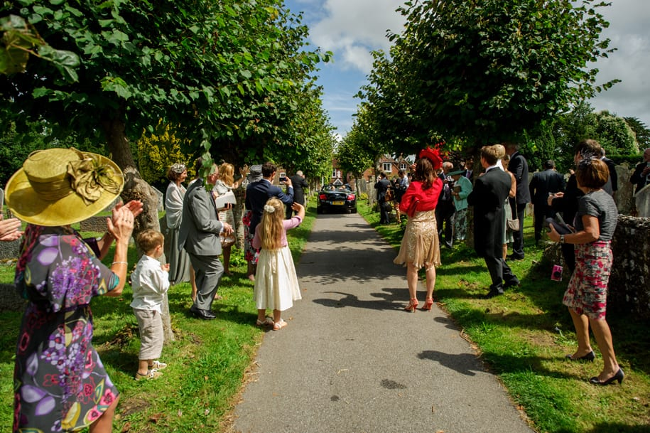Bride and groom drive away from Ditchling church