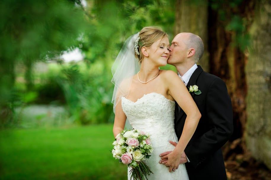 Groom kisses bride at Ridge Farm