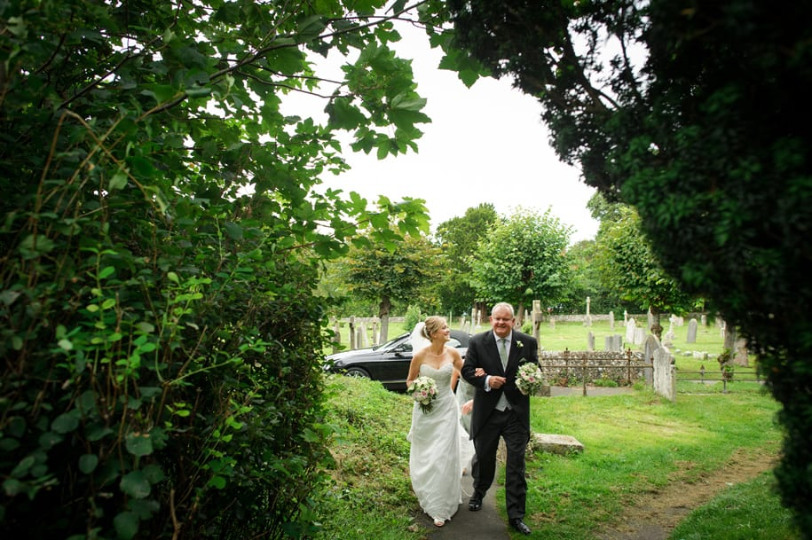 Bride walsk thought the churchyard with her father
