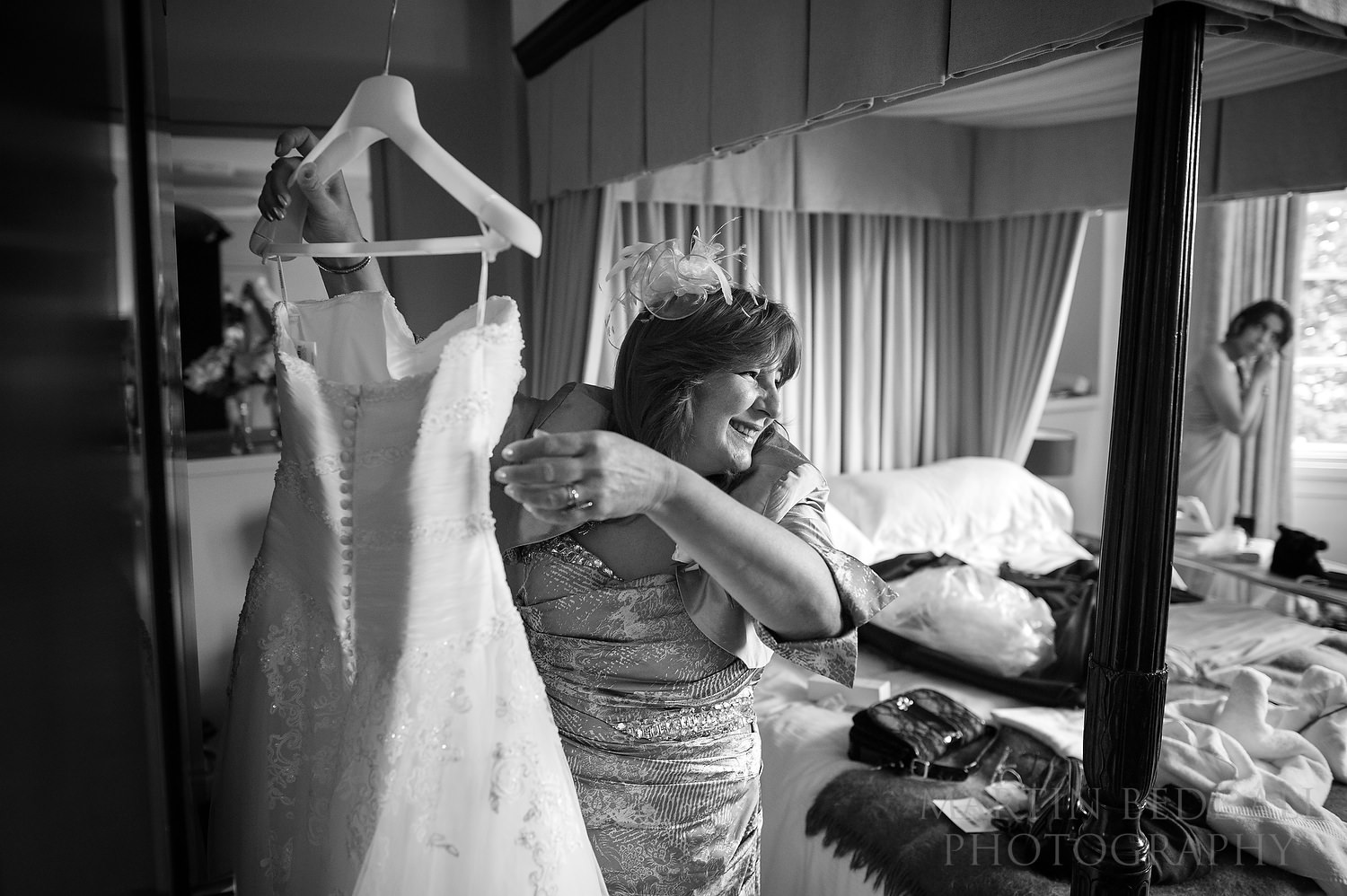 Bride's mother reaching for her dress